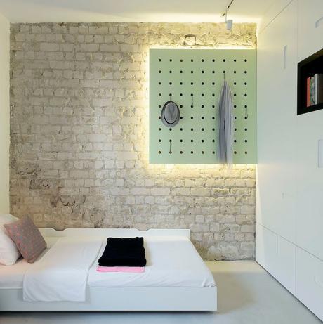 chambre sans fenêtre mur brique néons lumineux lit double