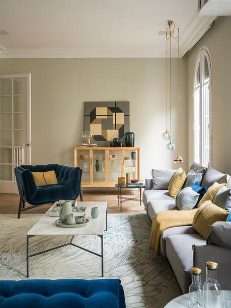 salon cosy gris canapé tapis motif plume paon fauteuil velours bleu foncé