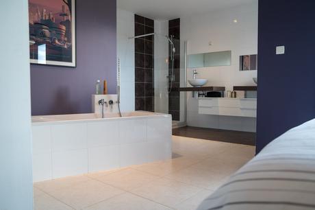 salle de bain ouverte baignoire îlot en carrelage blanc