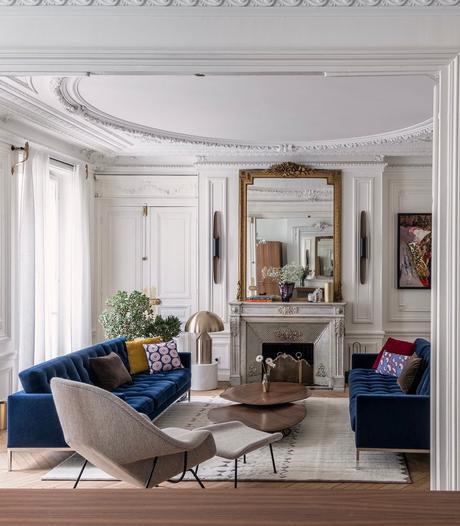 salon style paris canapé velours bleu cheminée marbre blanc miroir époque doré