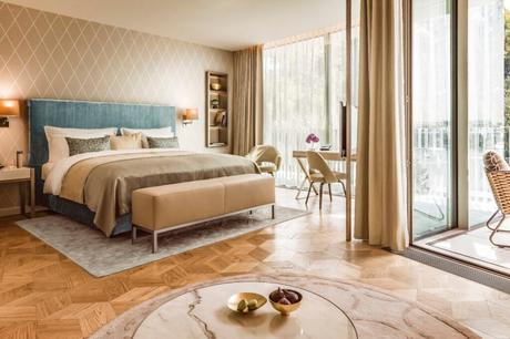 chambre hôtel élégant sobre beige sommier bleu velours parquet bois