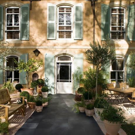 terrasse noire carre maison volet bleu pastel banc bois buisson