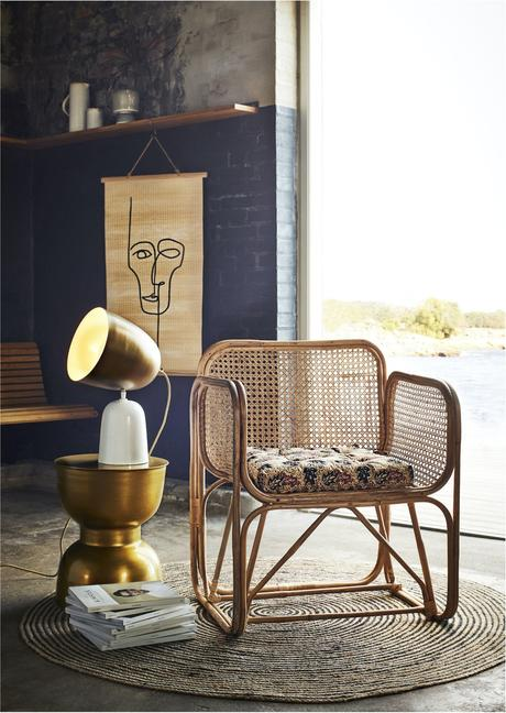 fauteuil en cannage mur en brique noir tapis rond rotin