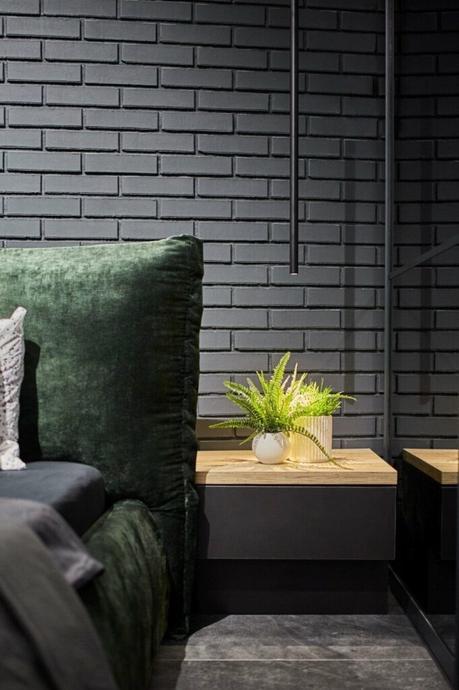 chambre lit velours vert mur briques noires déco masculine