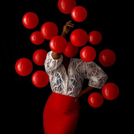 Des grappes de ballons brillants enveloppent la photographe Fares Micue dans ses autoportraits expressifs