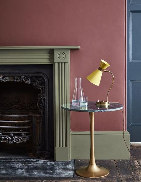 salon rustique cheminée vert kaki mur terracotta table basse ronde laiton marbre noir