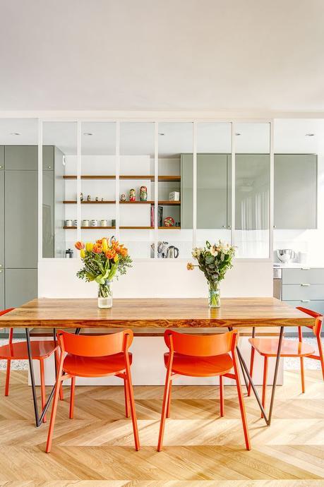 salle à manger table bois chaise orange fluo verrière blanche