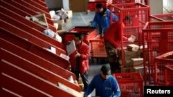 Les livreurs déplacent des colis d'une bande de tri automatisée vers des chariots dans un centre logistique intelligent de JD.com lors du festival du shopping Singles Day, à Pékin, en Chine, le 11 novembre 2020. REUTERS / Tingshu Wang
